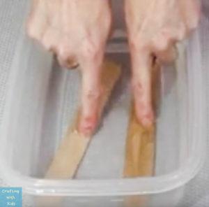 soaking craft sticks in water
