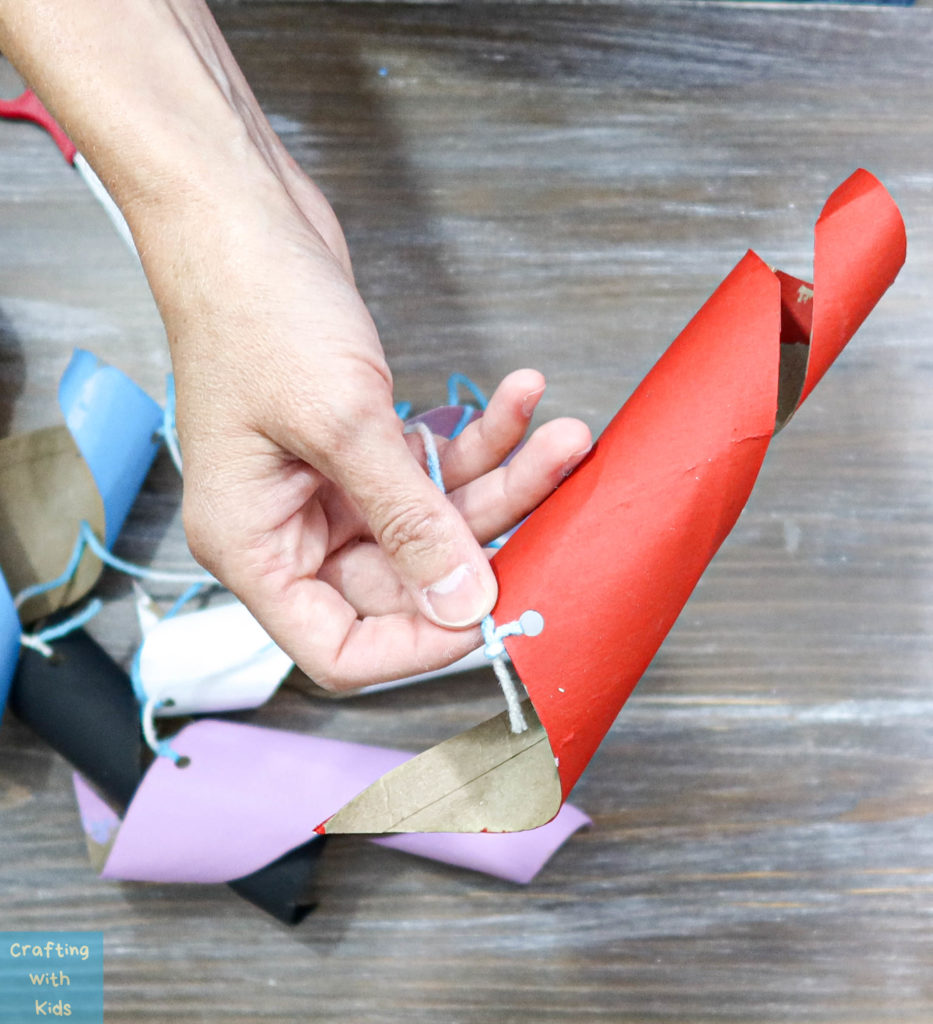 attaching string to toilet paper tubes