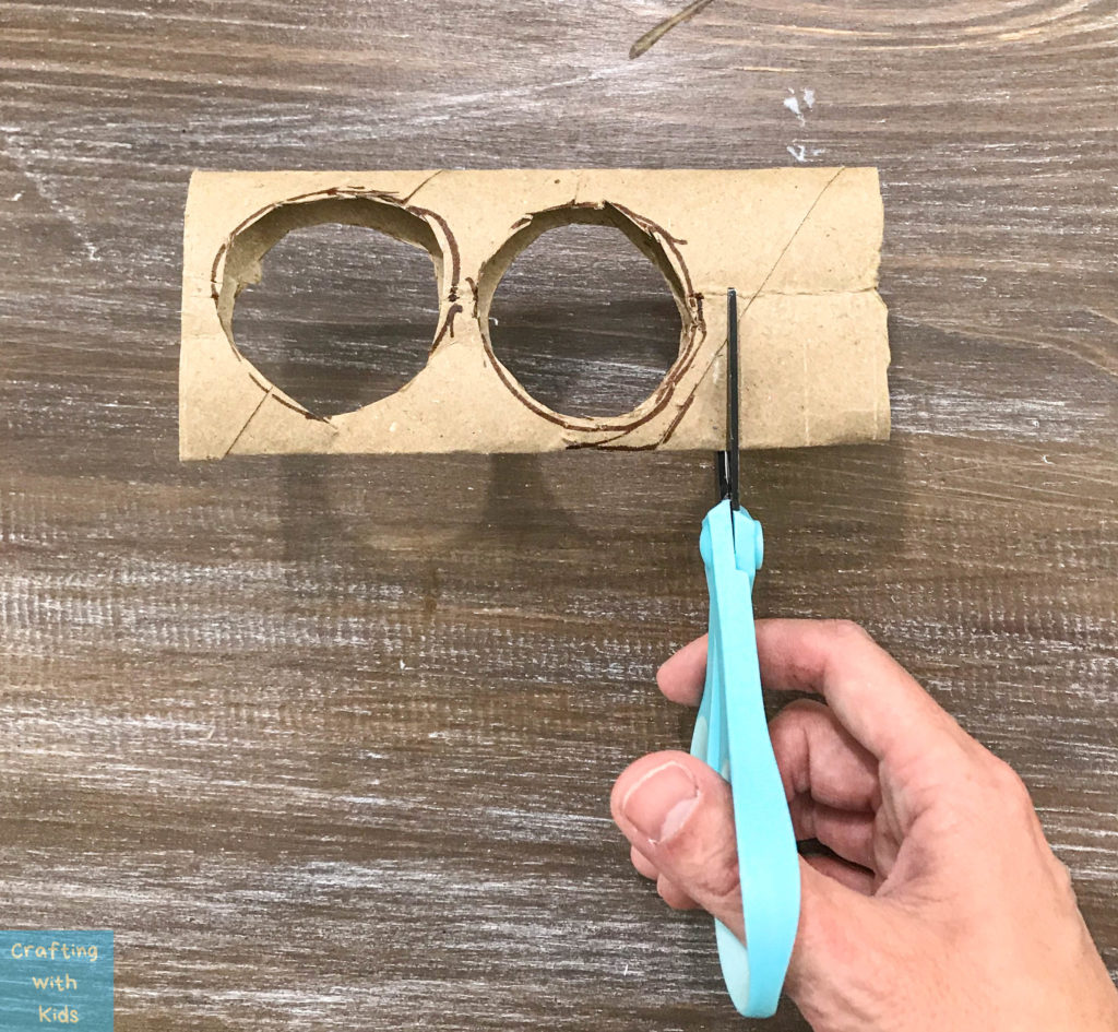 cutting the end off of the toilet paper binoculars