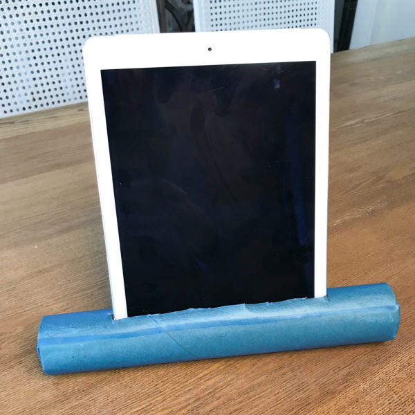 DIY vertical tablet stand from a paper towel roll