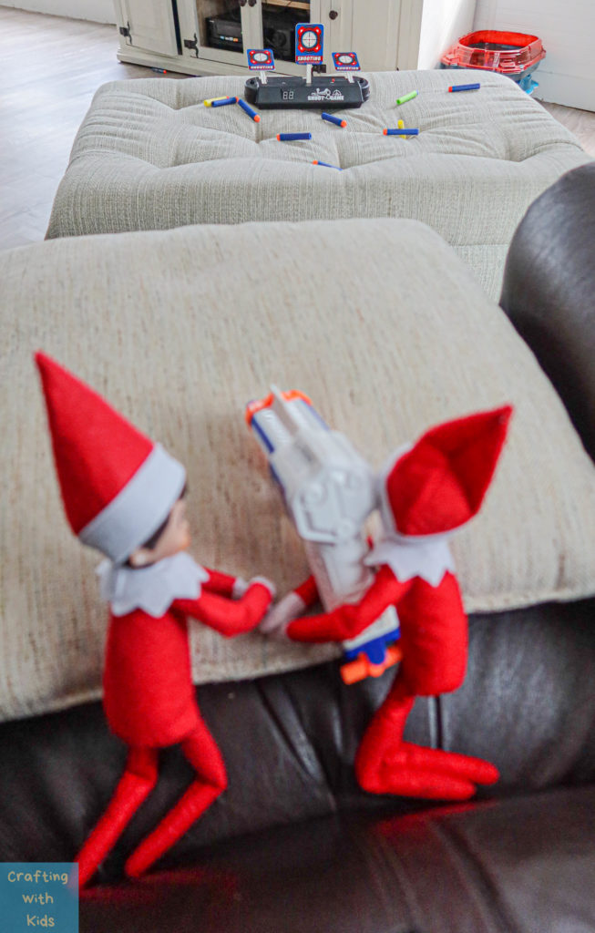 two elf on the shelf's with nerf guns