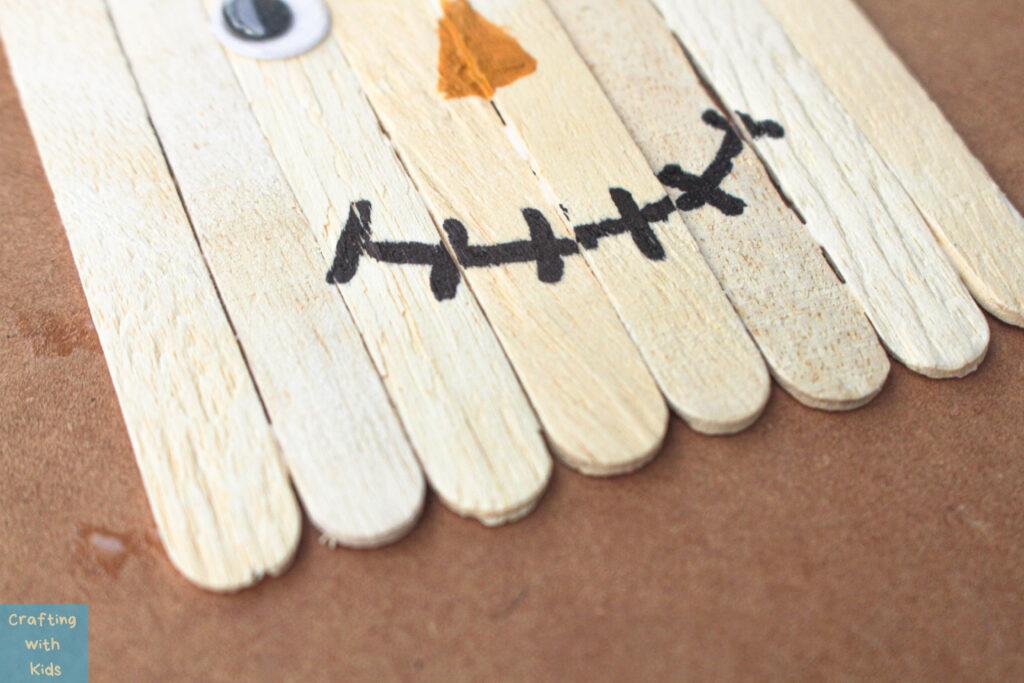 drawing mouth on popsicle stick scarecrow
