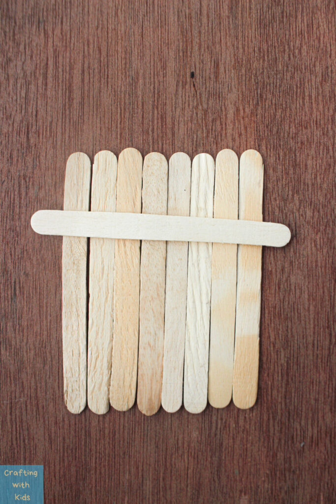 arranging popsicle sticks to make a fall craft