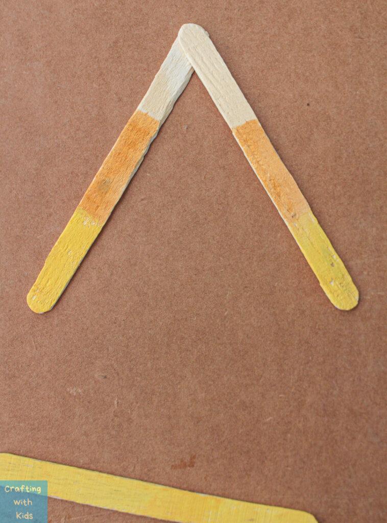 assembling candy corn popsicle sticks