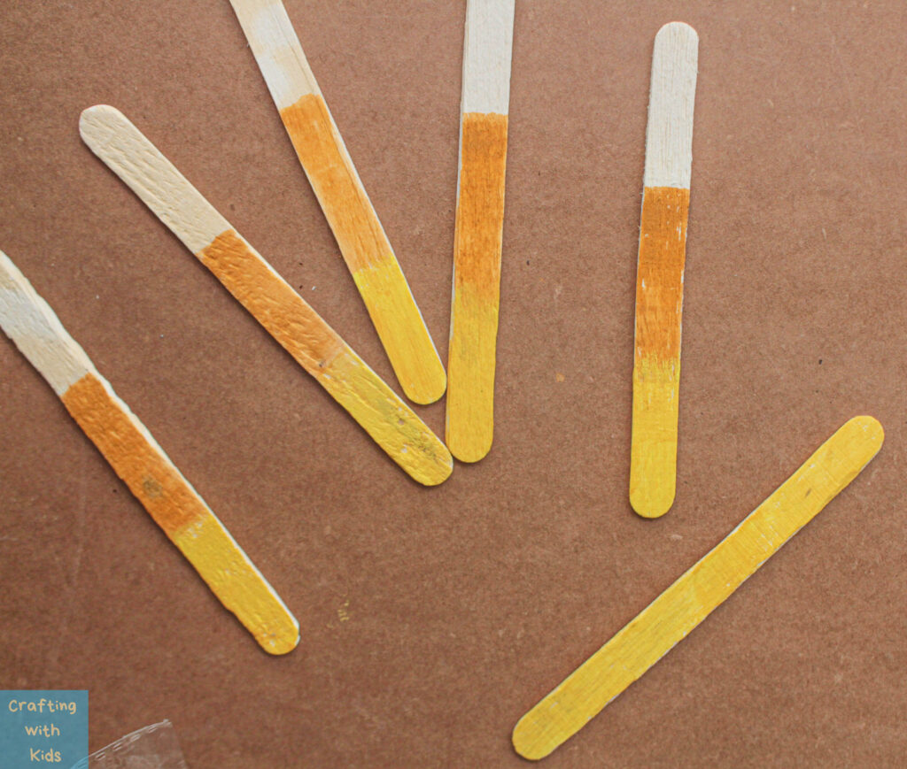 painting popsicle sticks to look like candy corn