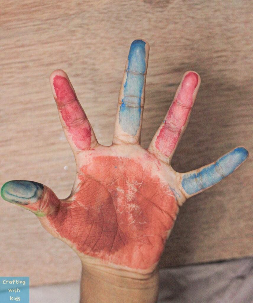 paint on child's hand for handprint Turkey craft
