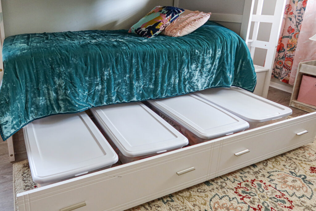 Under the bed storage idea with storage bins on a trundle